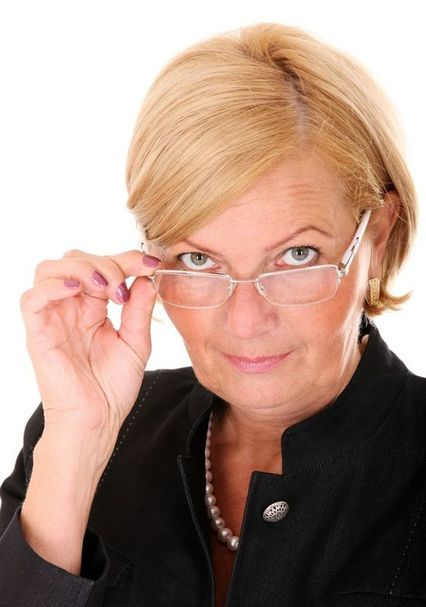 Picture of white professional woman looking over the top of her glasses.